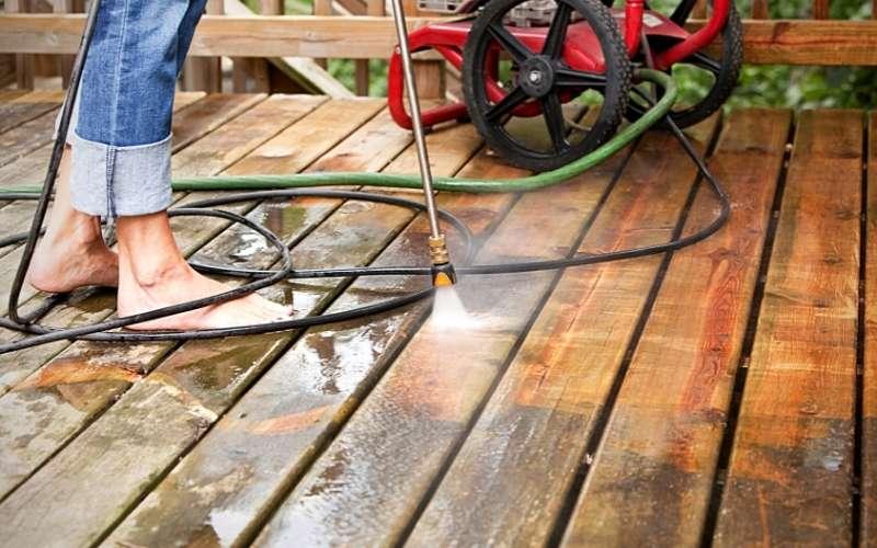 woman pressure washing a deck